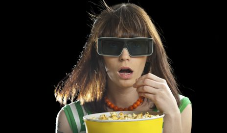 Woman wearing 3D glasses and eating popcorn