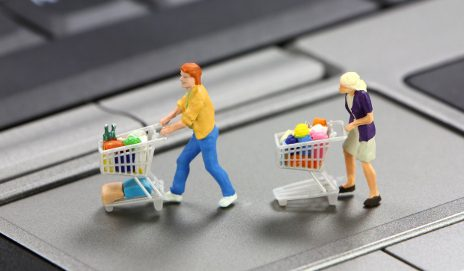 Plastic characters pushing shopping trolleys on laptop