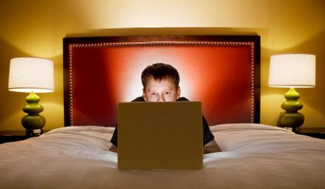 Man working on laptop on hotel bed