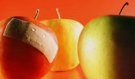 Three apples, with a plaster on one