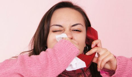 Female blowing nose on the phone